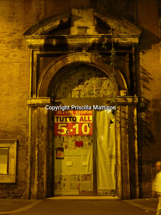"""Rome, Italy - October 6, 2012:  A man walks by a building entrance with a pediment.  The sign on the glass door reads """"Ultimi Giorni"""" (""""Last Days"""")."""