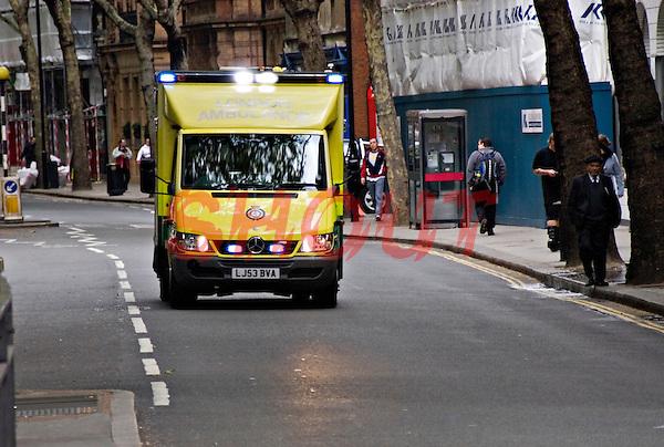 Ambulance on emergency call driving driving through traffic London, UK