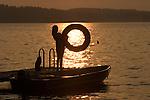 Girl holding innertube, silhouetted in sunset. Lake, NH