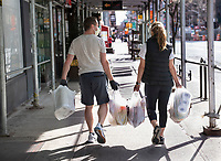 New York City, New York, Coronavirus in New York. A couple stocks up on groceries. It's now recommended to wear a face mask when out in public.