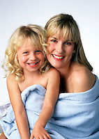 A smiling mother and daughter cuddling in a towel.