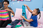 4 year old girl at home with mother, learning how to fold clothes, modeling imitation