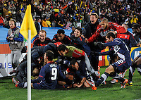 Michael Bradley of USA is piled on by team-mates after scoring the equaising goal