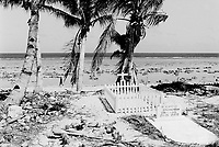 Republic of Nauru. Central Pacific. Nauru is a tiny island (21 square-km).  Coral pinnacles in the pacific ocean at low tide. A woman walks on the shore. A grave of man in a cemetery near the seaside. In memory of benjamin Maorgan born  died dates. © 1999 Didier Ruef