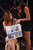 Girls sit outside a girlie bar in Hong Kong's Wanchai District reading the newspaper about the murderof sex workers.  A gruesome double murder was discovered yesterday of likely sex workers allegedly by a British banker who lived in the Wanchai District.<br /> <br /> 02-Nov- 2014
