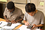 Education High School Mathematics class two male students working individually at table using calculators horizontal