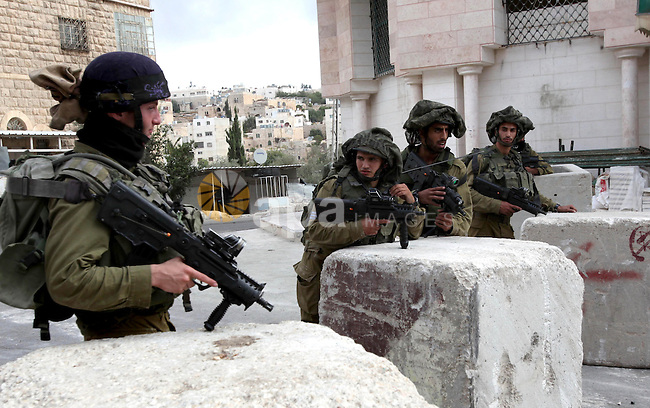 Israeli soldiers gather before starting a patrol in the West Bank city of Hebron, Monday, Sept. 23, 2013. Unknown gunmen shot and killed an Israeli soldier in the biblical city of Hebron in the West Bank on Sunday, and troops are searching for the shooter, the military said. Photo by Mamoun Wazwaz