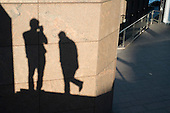 Self-portrait: photographer and shadow figures on a wall, London.