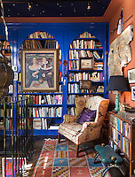 The Moroccan theme extends to the mezzanine library with bookshelves painted an intense ultramarine and lit by a large ceiling lantern