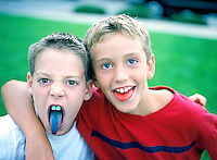 Young boys playing in summer time with tougues colored red and blue