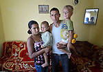 Feride Ramadan Mehmed (left) and her husband Mehmed hold their children Birdzhan, 1, and Erdzhan, 3, in their house in the Maxsuda neighborhood of Varna, Bulgaria. They are Turkish-speaking Roma, and were violently driven out of one neighborhood by racist gangs. They took refuge in a United Methodist Church for a year before finding this small house to rent.