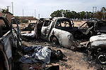 Burned cars and bodies lie near the drainage pipe where Col. Muammar Gaddafi was found, one day after his capture and death in Sirte, Libya, Oct. 21, 2011. Gaddafi's convoy was hit by a NATO airstrike about a half hour after they left District 2 where he was hiding in Sirte. Two revolutionary brigades battled members of the convoy before finding Gaddafi hiding in the pipe.