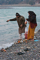 India, Rishikesh.  Man Pouring Early Morning Offering of Milk to the River Ganges (Ganga).