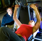 Personal trainer Brian Fritz assists coworker Kristin Haanstad during her workout at Capital Fitness in Madison, Wis. on Wed. Jan. 16, 2008