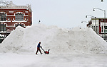 While helping the city dig out from heavy snowfall, Ed Dieleman walks past a 20-foot heap of snow in the town square of Oskaloosa, Iowa on Wednesday, February 2, 2011.  Many Oskaloosa residents are saying the heaps are the largest they've ever seen.