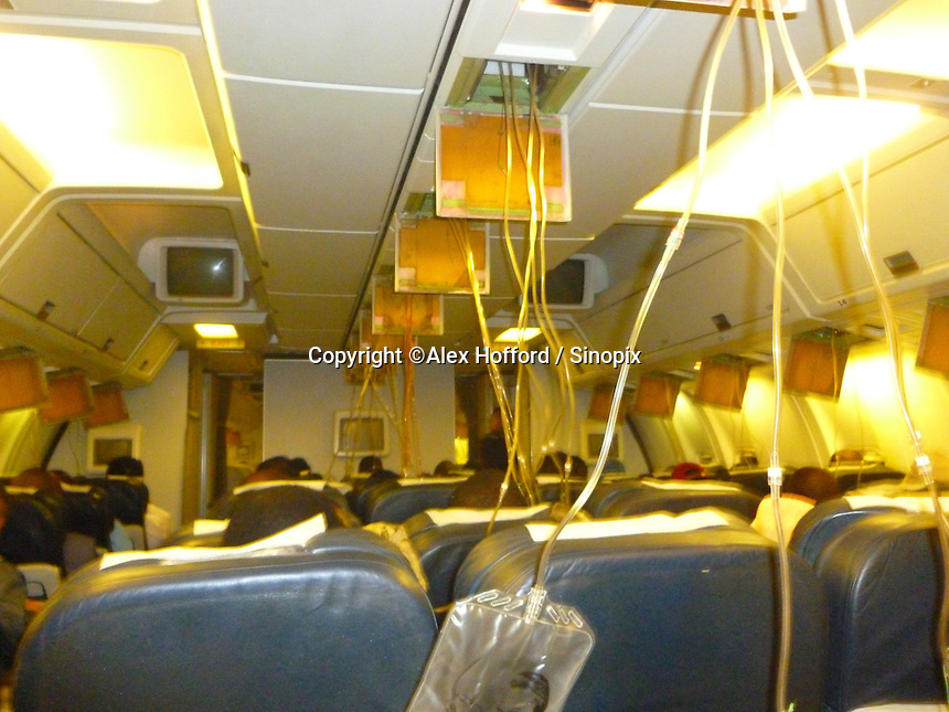 A photo taken by a passenger of Ethiopian Airlines flight ET609 from Hong Kong to Addis Ababa shows the aircraft cabin with oxygen masks deployed during a two hour diverted flight back to Hong Kong, China, 14 June 2014. According to passengers, the aircraft lost cabin pressure, dumped fuel over the ocean, and had to return back to Hong Kong where ten fire trucks as well as other emergency service vehicles were waiting. The plane landed safely, and no one was hurt.