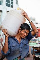 Myanmar, Burma, Yangon.  Stevedore Carrying Cargo from Ship to Shore.