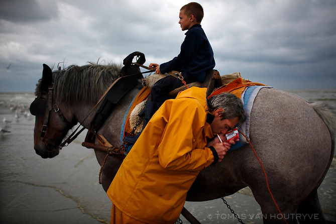 A shrimp fisherman ducks behind his horse to light a cigarette while his son sits on top of the horse in Oostduinkerke, Belgium on 25 August, 2008. The fishermen ride into the sea on horseback and pull nets through the shallow water.