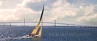 An Americas Cup yacht approaches the Newport Bridge from the North. Many of these historic yachts can still be seen plying the waters off Newport and are available for cruises.
