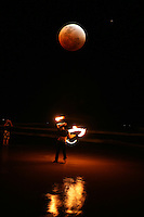 Fire Twirler during the lunar eclipse on Nobby's Beach, Newcastle, New South Wales