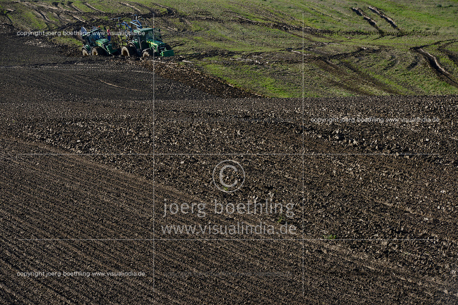 Germany, farming with extreme wet soil conditions after heavy rainfall for days, two big John Deere tractors deadlocked in the furrow