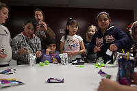 Children, amny  of whom are american citizens at an HOLA meeting in Painesville, Ohio. Hola meets weekly and people share deportation stories and inform other community members of thier ongoing immigration struggles. Thier children also come to the meetings at  LifeSpring HUB Christian Church. The youngest partcipate in activities in an adjacent storefront. March 25, 2014. Photo by Brendan Bannon.