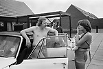 1970s UK, professional middle class couple outside their new modern home on a recently built new housing development. Hanging out with the new baby in arms by their car that is parked out side their home. The man behind the shirtless, its summer car driver is a friend up for the day to see the new house. 1977 Milton Keynes Buckinghamshire.