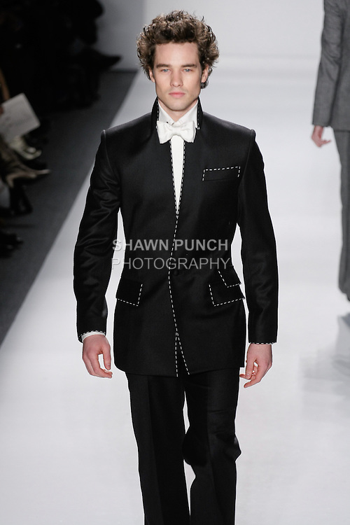 """Model walks runway in a men's black loro piana cashmere/wool upturened peak lapel suit w/ivory top-stitching, ivory italian silk dupioni dress shirt+bow tie, from the Zang Toi Fall 2012 """"Glamour At Gstaad"""" collection, during Mercedes-Benz Fashion Week New York Fall 2012 at Lincoln Center."""