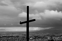 A wooden cross, pointing out a local church, is seen placed above the large outskirts in the south of Bogota, Colombia, 31 May 2010. Hundreds of Christian belivers, joined in nameless groups, gather every week in unmarked home churches dispersed in the city outskirts, to carry out prayers of liberation and exorcism. Community members and their religious activities are usually conducted by a charismatic pastor or preacher. Using either non-contactive methods (reading religous formulas from bible, displaying Christian symbols and icons) or rough body-pressure-points techniques and forced burping, a leading pastor commands the supposed evil spirit, which is generally believed to come from witchcraft, to depart a person's mind and body. The demon's expulsion often consists of multiple rites and may last for several months.