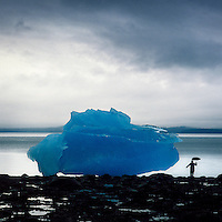 An explorer is drawfed by an iceberg from the LeConte Glacier in Alaska.