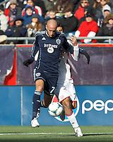 Sporting Kansas City defender Aurelien Collin (78) and New England Revolution forward Juan Toja (7) battle for the ball.  In a Major League Soccer (MLS) match, Sporting Kansas City (blue) tied the New England Revolution (white), 0-0, at Gillette Stadium on March 23, 2013.