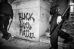 NEW YORK, NY — OCTOBER 27, 2020:  NYPD police officers carrying batons pass in front of freshly painted graffiti during a protest against police brutality, in response to the shooting of Walter Wallace Jr. by Philadelphia police officers the prior day, across from City Hall on October 27, 2020 in New York City.  The confrontation, recorded on a now viral video posted to social media, shows Wallace, a 27 year-old Black man who family members said was in the midst of a mental health crisis, holding a knife as two police officers shot and killed him.  Photograph by Michael Nagle