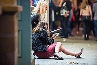Saturday  17 December 2016<br /> Pictured: Girls sit on the street on Swansea's Wind street <br /> Re: Swansea City Centre and the notorious Wind street, often nicknamed 'Wine Street' is packed full of Christmas jumpers and glitzy dresses as thousands head to office dos across the UK in the biggest party night of the year.