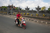 Bali, Indonesia.  Road safety.  Father and Daughter on Motorbike, no helmets.