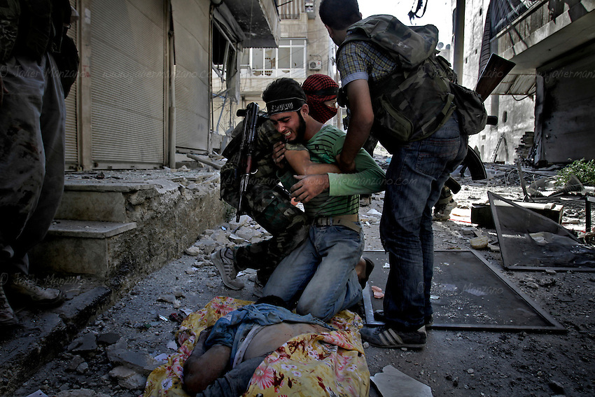 A Free Syria Army soldier reacts to the death of one of his comrades who died attempting to take out a Syria Army tank during intense clashes in the al-Qoob district of Aleppo. ..© Javier Manzano.