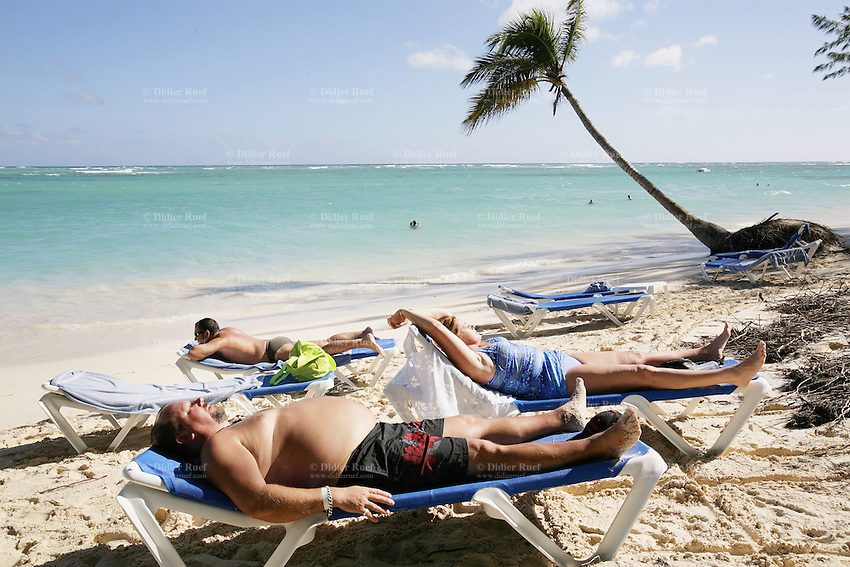 Dominican Republic. La Altagracia Province. Coastal resort of Punta Cana. Playa Bavaro. El Cortecito. A stout white man and a fat woman lay back on a deckchair near the beach. They are enjoying the sun and sunbathes. Blue sky. Punta Cana is well-known for its beaches and palm trees where meet whites sands and warm turquoise water from the Atlantic Ocean.  © 2006 Didier Ruef