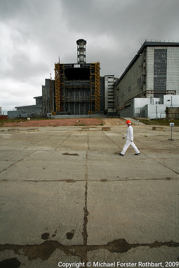 """Chernobyl plant worker Sergei Koshelev crosses the high-radiation zone beside Chernobyl's ground zero. The concrete and lead Sarcophagus encloses the ruins of the reactor hall where the meltdown occurred. The Sarcophagus leaks and is structurally unstable. Construction workers preparing foundations for a replacement """"New Safe Confinement"""" can hit their maximum daily dose in two to three hours.  <br /> ------------------- <br /> This photograph is part of Michael Forster Rothbart's After Chernobyl documentary photography project.<br /> © Michael Forster Rothbart 2007-2010.<br /> www.afterchernobyl.com<br /> www.mfrphoto.com <br /> 607-267-4893 o 607-432-5984<br /> 5 Draper St, Oneonta, NY 13820<br /> 86 Three Mile Pond Rd, Vassalboro, ME 04989<br /> info@mfrphoto.com<br /> Photo by: Michael Forster Rothbart<br /> Date: 7/2009    File#:  Canon 5D digital camera frame 72232<br /> ------------------- <br /> Original caption: .Sergei Koshelev, videographer for the Chernobyl SIP PMU (Shelter Implementation Plan Project Management Unit) visits the high-radiation zone just west of the Chernobyl Nuclear Power Plant's 4th Block Shelter (also called the Sarcophagus). Workers refer to the area inside the final high-security perimeter as the """"local zone,"""" where they are doing groundwork for construction of the New Safe Confinement super-structure that will replace the Sarcophagus.."""