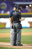 Buies Creek Astros manager Morgan Ensberg (14) goes over a lineup change with home plate umpire Ben Phillips during the game against the Winston-Salem Dash at BB&T Ballpark on May 5, 2018 in Winston-Salem, North Carolina. The Dash defeated the Astros 6-2. (Brian Westerholt/Four Seam Images)