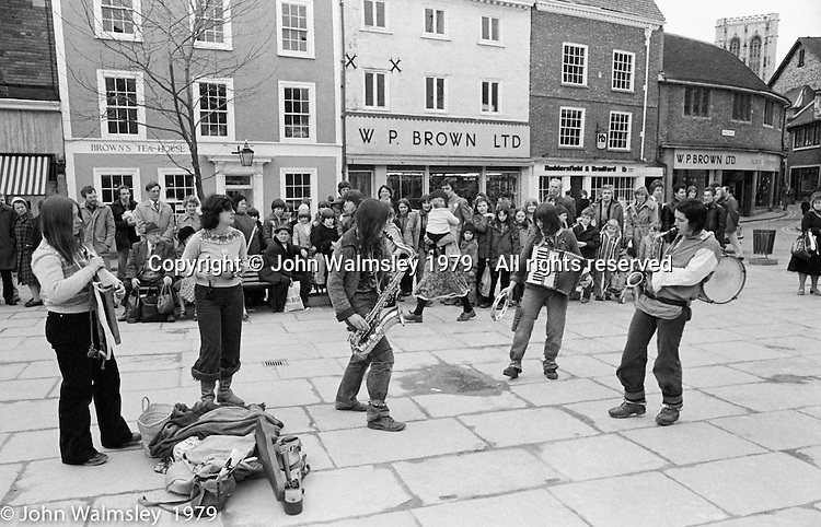 The York Street Band playing in York, March 1979.  Dena Attar on saxophone, Sarah Kemp on washboard, then the three members of the YSB: Sarha Moore (percussion), Anthea Gomez (accordian) and Ros Davies (saxophone & drum on back).  Sarha Moore and Ros Davies went on to play in The Bollywood Band, and Ros also joined the Grand Union Band, in London.  Anthea Gomez went on to write and play music for the theatre and then BBC Drama before changing direction.