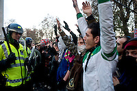 Students raise their arms to show their nonviolence to police during a student demonstration in Westminster, central London on the day the government passed a bill to increase university tuition fees. .
