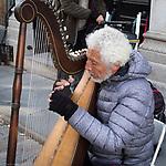 Elderly street musician playing harp. Old Quebec City.