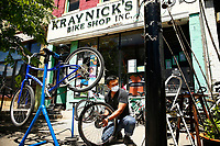 Rocky Cristobal, owner of Kraynick's Bike Shop, repairs bikes outside on the sidewalk in the Garfield neighborhood on Thursday May 21, 2020 in Pittsburgh, Pennsylvania. (Photo by Jared Wickerham/Pittsburgh City Paper)