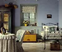 A traditional blue bedroom with part panelled walls. An iron frame single bed stands in one corner. A dressing table with a floral pattern cloth and a chair upholstered in a matching fabric stands nearby