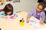 Education Preschool 3 year olds two girls coloring with crayons using opposite hands (right or left hand to hold crayon) art activity