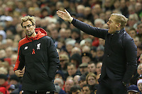 Liverpool Manager Jurgen Klopp watches play by peering around Swansea City Manager Garry Monk during the Barclays Premier League Match between Liverpool and Swansea City played at Anfield, Liverpool on 29th November 2015