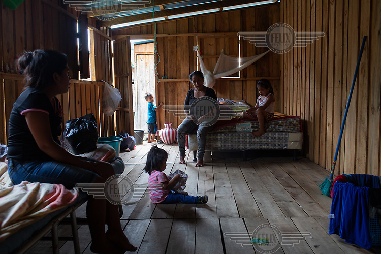Evelyn Janeth Funes (left), 20, and her one-year-old daughter Camila (sitting on the foor), visit Evelyn's mother Gregoria Montejo, 41, and her youngest sister Adriana Funes, 6, in their unit at the Single-Family Transitional Shelters in Escuintla City.