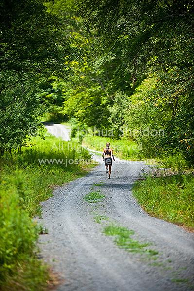 Female athlete running down gravel road