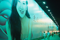 China. Province of Zhejiang. Hangzhou. Night time. People walk near a giant publicity campaign. © 2004 Didier Ruef