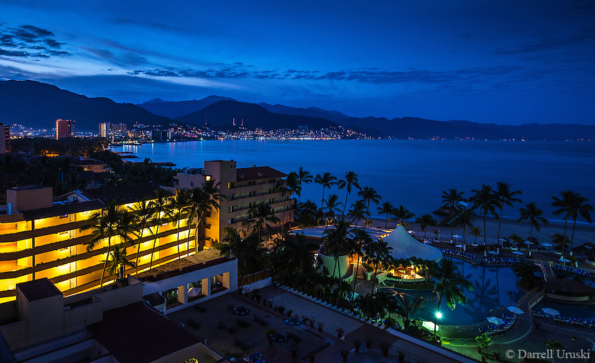 Fine Art Landscape Photograph. Night scene of Puerto Vallarta with its city lights surrounding Banderas Bay In the state of Jalisco Mexico. The glowing city lights of Puerto Vallarta, the blue pastel shades of the mountains, and the palm trees  reveal the beauty of this charming Pacific ocean scene.