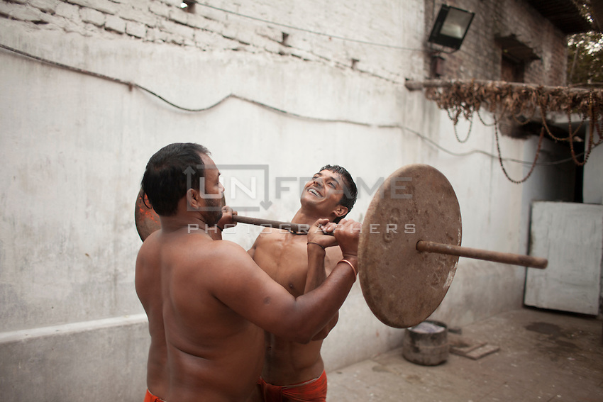 The Pehlwan (an Indian wrestler) Jawla Trwatri helps his son to lift the gym weight during a training session. Kolkata, India